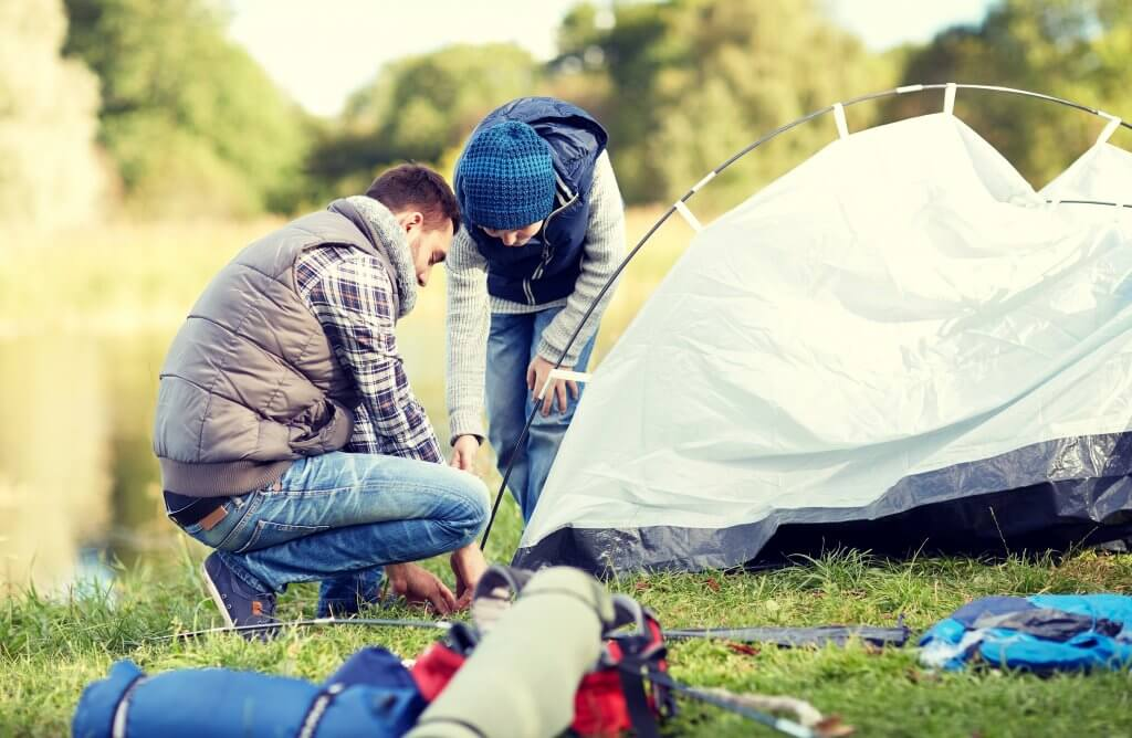 happy father and son setting up tent outdoors PWRZA4N