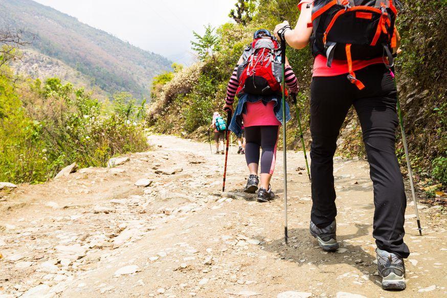 a group of people trekking on dirt road in nepal PV3DFYJ 1