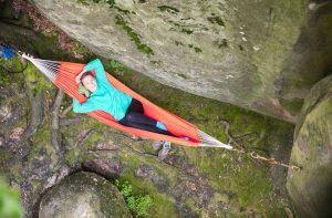 cheerful young woman relaxing in hammock near P53DS6N