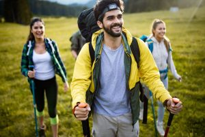 group of hikers walking on a mountain and smiling A8QM735