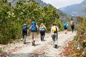 a group of people trekking on dirt road in nepal PFYBHTS